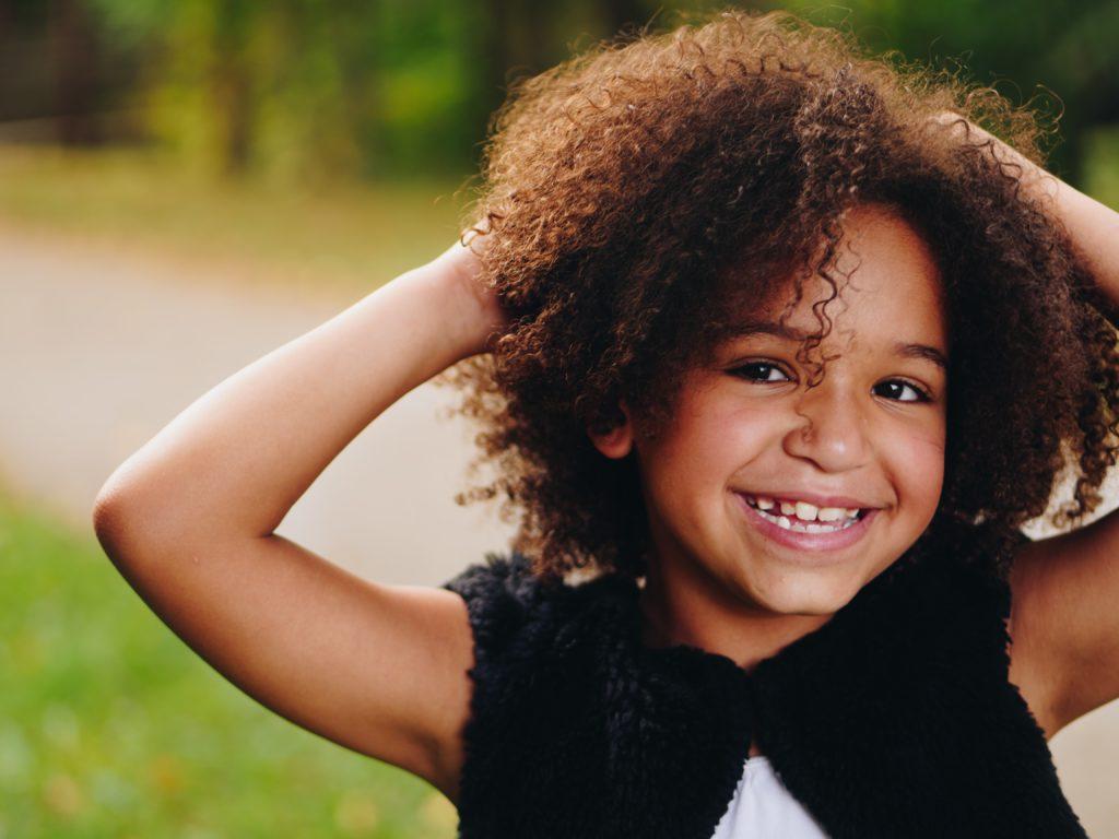 Petite fille souriante se tenant la tête avec les mains