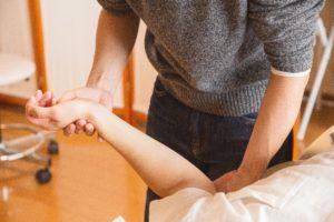 Kinésiologue qui pratique le toucher musculaire du bras sur un patient
